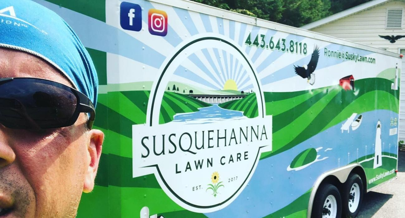 Ronnie Spurlin, owner of Susquehanna Lawn Care standing in front of one of their work vehicles.