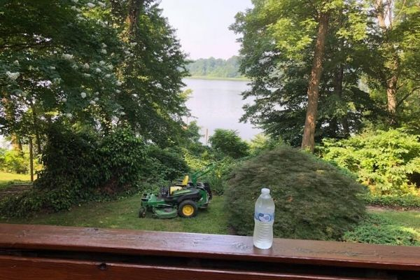 A Susquehanna Lawn Care's lawn mower sitting in the back yard of a customer.