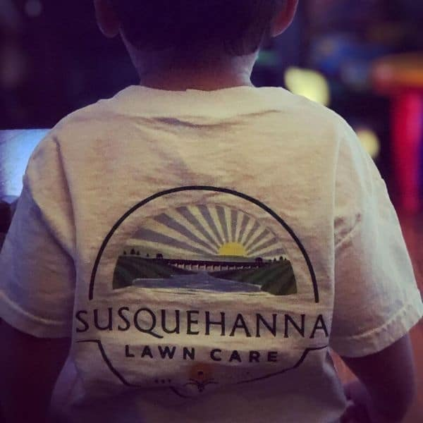 A child wearing a Susquehanna Lawn Care's tshirt.