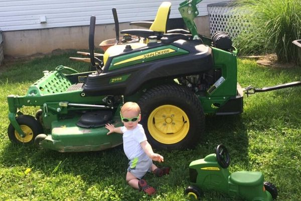 One of Ronnie Spurlin's, owner of Susquehanna Lawn Care, children posing with a large commercial mower.