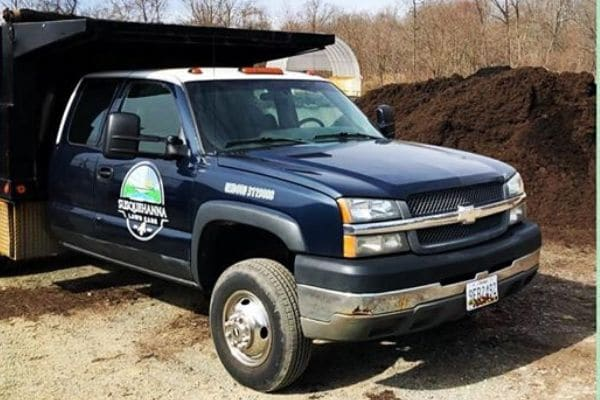 A black Susquehanna Lawn Care work truck. Their logo is printed on the side of the truck.