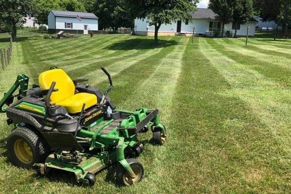 One of Susquehanna Lawn Care's commercial mowers sitting in the lawn of a customer after a completed mowing service. Behind the mower, the grass is neatly mowed and has neat mowing stripes.