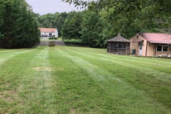 A large back yard that has recently been serviced by Susquehanna Lawn Care. The grass has been mowed and all leaves and debris has been cleaned up.